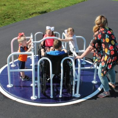 kids playing on wheelchair accessible merry go round