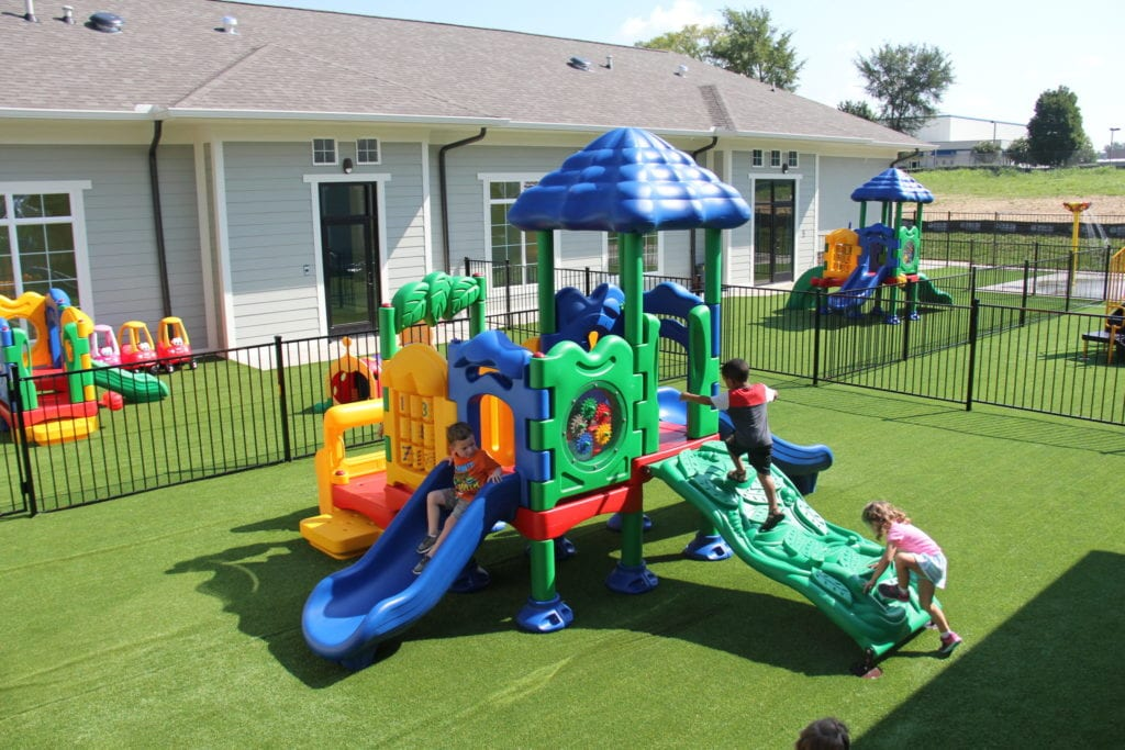 UltraPlay Discovery Center Playground from a high angle perspective on synthetic lawn turf safety surfacing, surrounded by aluminum black fencing