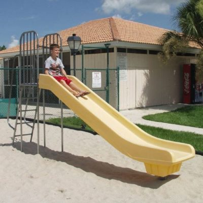 Child sliding down a slide in yellow