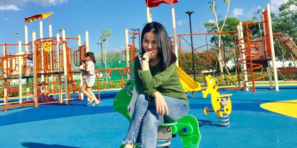 Woman Sitting on a Spring Rider Smiling on a Playground