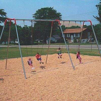 Kids swinging on a swingset in a park with wood mulch